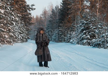 Portrait of senior woman fur coat and hat standing in cold winter snow covered forest, telephpto, wide angle