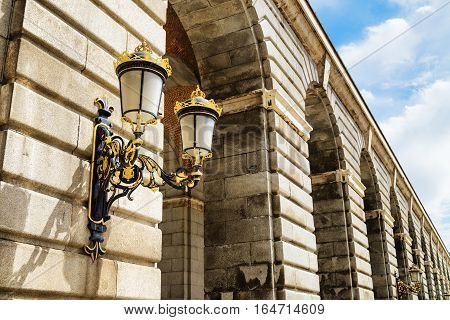 Traditional Forged Street Lamp On A Column Of The Royal Palace Of Madrid In Spain