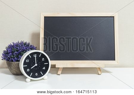 Closeup alarm clock for decorate show 8 o'clock with wood black board on white wood desk and cream wallpaper textured background selective focus at the clock