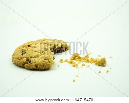 Chocolate chip cookie and crumbs on white background