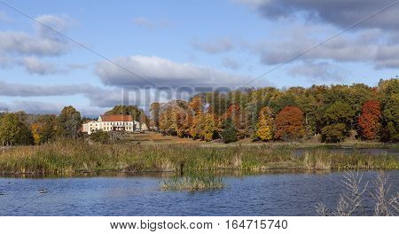 ROSLAGEN, SWEDEN ON OCTOBER 10. View in the morning, colorful leaves in the trees, a sunny estate on October 10, 2016 in Roslagen, Sweden. Lake this side. Editorial use.