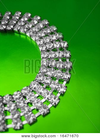 Close up of diamond necklace on green background