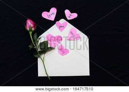 happy valentine day i love you word message on heart and rose out of envelope on background black