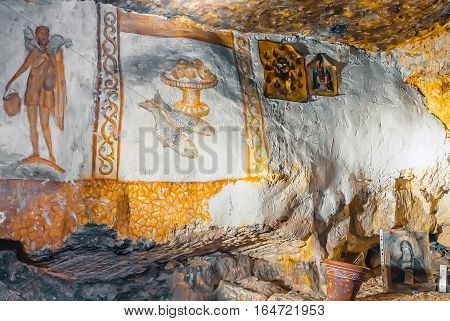 Moscow region, Russia - December 24, 2016: Siagne - Moscow system of artificial caves-quarries. Religious Orthodox icons and sacred paintings on the walls of the grotto in  Siagne caves-quarries.