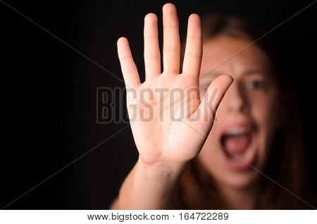 Young woman saying no shielding with flat hand
