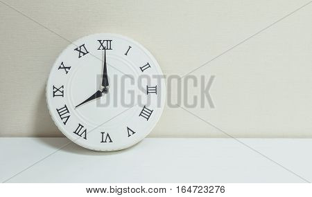 Closeup white clock for decorate show 8 o'clock on white wood desk and cream wallpaper textured background with copy space