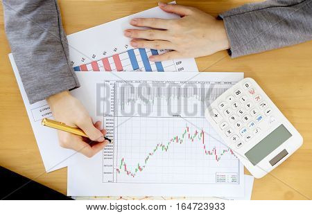 Businesswoman using calculator while analyzing graphs, business's plan