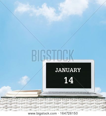 Closeup computer laptop with january 14 word on the center of screen in calendar concept on blurred wood weave table and book on blue sky with cloud textured background with copy space