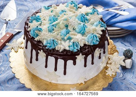 Beautiful cream cake decorated with chocolate leaks cream and sugar snowflakes from mastic on the background of plates teaspoons and pallet knife