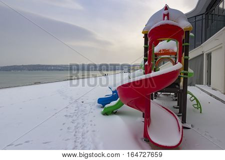 colorful children playground on the beach in snow