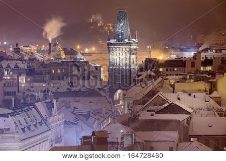 Winter view on Powder Gate and snowy rooftops at the Republic Square in Prague. In the distance you can see the National Monument in Vitkov. Old Town is a famous destination in Prague. Czech Republic
