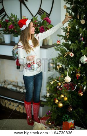Attractive young smiling brunette in red cap decorates christmas tree