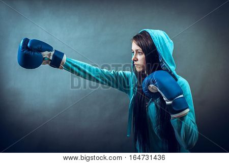 Young woman training punch boxing gloves, in studio