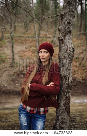 young beautiful woman in burgundy hat and sweater posing in the forest among the trees