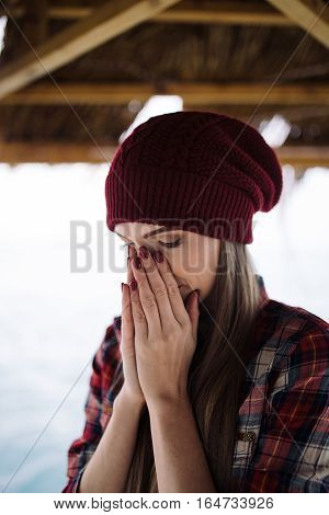 sad young woman in burgundy hat covers face with her hands