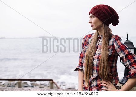 portrait of beautiful young woman in burgundy hat and plaid shirt against the backdrop of stormy sea
