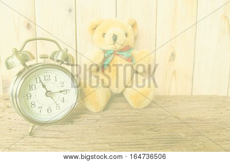 Old fashioned alarm clock and brown bear doll with color filter