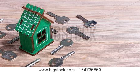 Home and keys on old wooden table