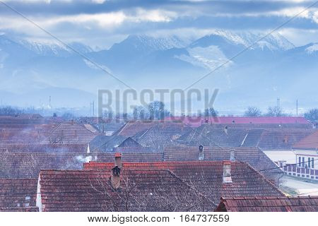Roof tops of village in Romania Brasov and Carpathians mountains. Picturesque panorama of Romanian Carpathians mountains. Rooftops of a traditional idyllic village at the foot of the Carpathian mountains on a winter day.