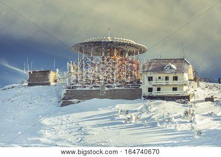 Buildings on Postavarul mountain top in the Romanian ski resort Poiana Brasov. The Postavarul peak covered by snow in the winter season.