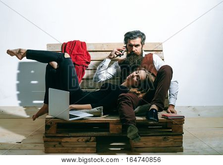 Young couple spend time together with laptop computer. Pretty girl or beautiful woman sleeps on knees of handsome man bearded hipster with beard talking on mobile phone on wooden pallet sofa