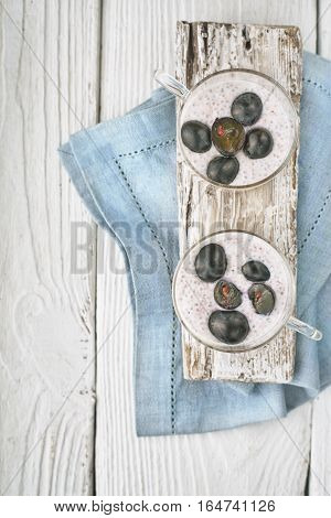Chia pudding with grapes on the white wooden table vertical