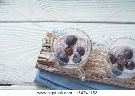 Chia pudding with grapes on the white wooden table horizontal
