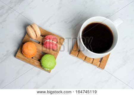 Sweet and colourful macaroons served on little wooden pallets with cup of coffee on a marble texture background. Traditional french dessert