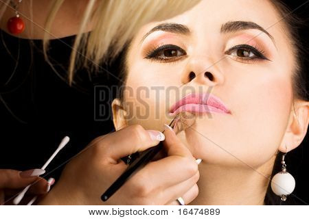 cosmetologist doing make-up for model with brush