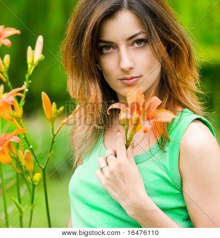 Krásná žena v zahradě s květinami