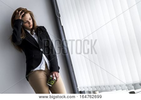 Young business woman taking a coffee break in her office, leaning against a wall, anxious