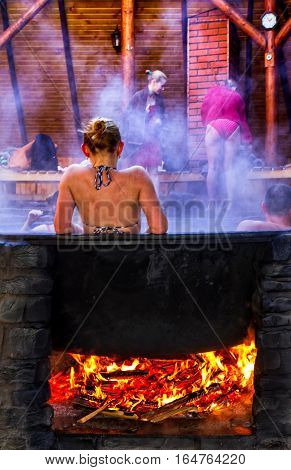 Lumshory Ukraine - January 10 2017: A woman bathes in a the cast iron vat with mineral water containing hydrogen sulphide. Water in cast iron vats heated to 40-45 degrees Celsius.