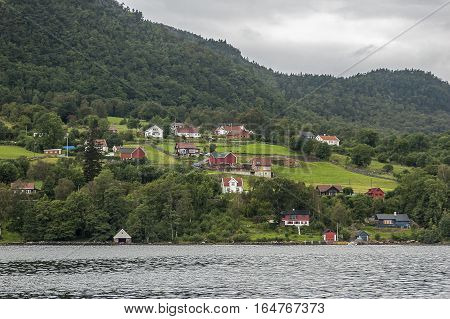Norway Lysefjord. Very rare residential villages on the shores of the fjord. Cloudy rainy day.