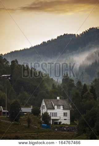 Norway early in the morning in a small village on the banks of Neroyfiord fog in the mountains . Wooden house.