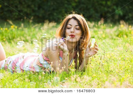 girl inflating soap-bubbles in field