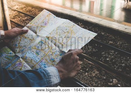 Young traveler holding travel map outside train window on a platform in the train station. Concept travel by train.