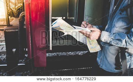 Young Man Get Into A International Train Alone  With Travel Map On A Platform In The Railway Station