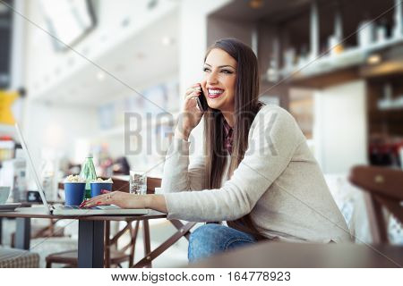 Young woman sitting in the cafeteria with laptop and using mobile phone