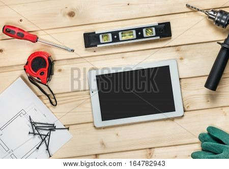 White tablet and set of hand construction tools to repair on a wooden surface: drill, pliers, self-tapping screws, roulette, level, draft, work gloves. Workplace carpenter. Top view