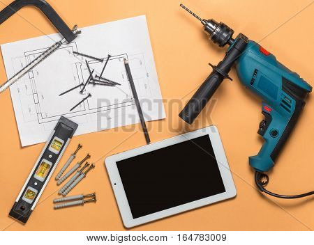 Set of construction tools to repair and white tablet on orange-brown table: drill, hammer, pliers, self-tapping screws, roulette, level, drawing, pencil. Top view.