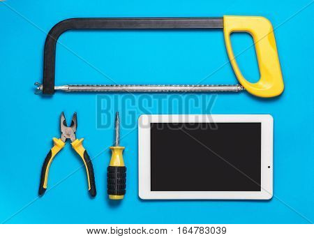 Tablet and set of construction tools to repair on a bluetable: drill, hammer, pliers, self-tapping screws, roulette, level, drawing, pencil. Top view.