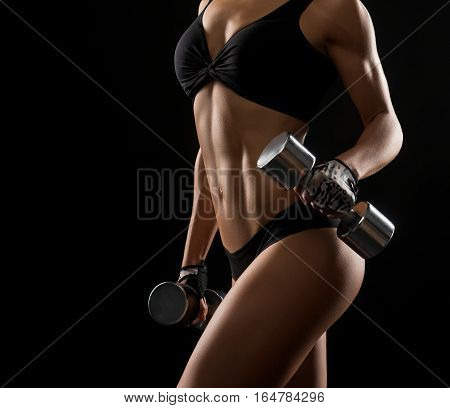 Unstoppable hardworker. Cropped closeup of s fitness woman with perfect strong muscular body posing with dumbbells in her hands
