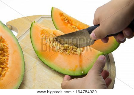 cantaloupe melon is being cut on a cutting board on a white background.