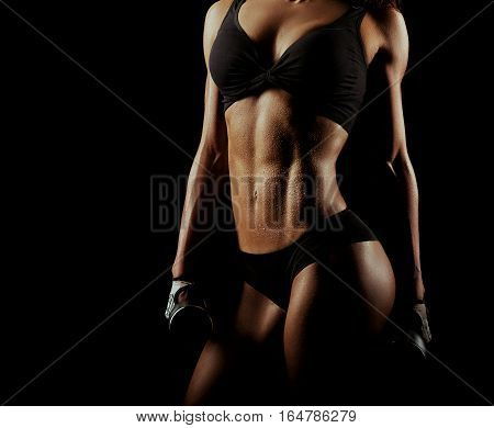 Nothing but perfection. Cropped studio shot of a wet muscular torso of a female fitness model after a workout with weights