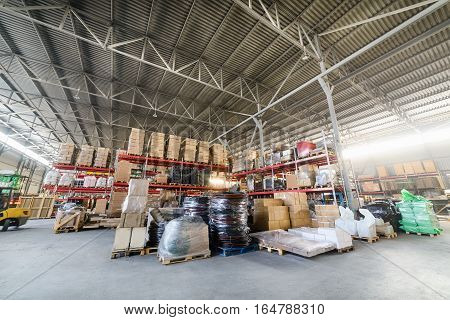 Large hangar warehouse industrial and logistics companies. Warehousing on the floor and on high shelves.