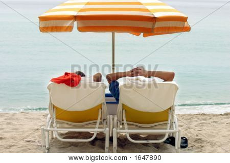 Couple Tanning On The Beach