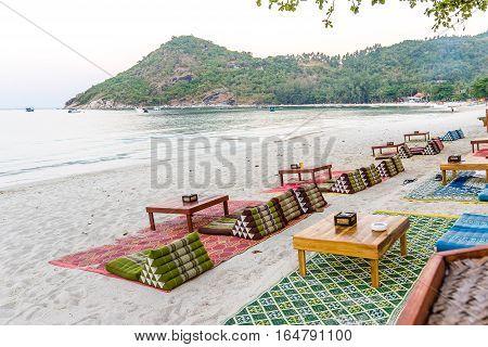 Carpets for lying down to dinner on a beautiful sandy beach in Thailand. The beach Ao Thong Nai Pan Yai at the Island Koh Pangan.