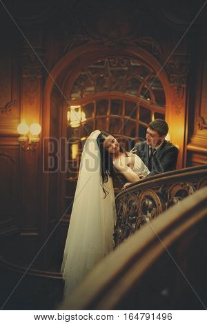 Bride Leans On Stair Railing In The Wooden Hall