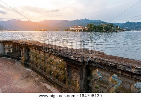 Island and mountains. Water and old stone railing. Trip to Isola Bella.