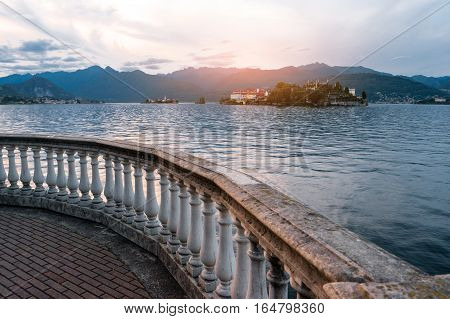 Water, mountains and sky. Old stone railing outdoor. Travel to Isola Bella.